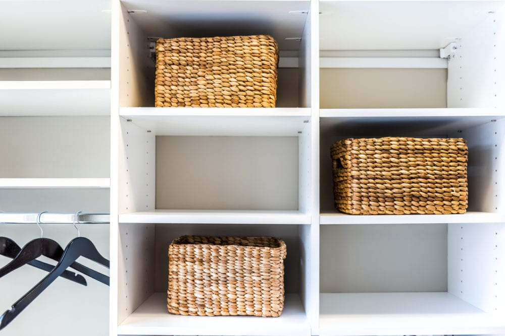 plain white shelves with woven baskets, making an organized closet